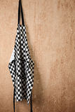 Chef's Apron. A chequered chef's apron hangs from a rusty nail on an old rendered wall Royalty Free Stock Photography
