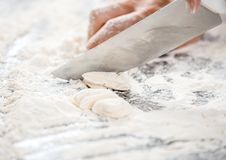 Chef's Hand Cutting Dough At Messy Counter. Cropped image of chef's hand cutting dough at messy counter in commercial kitchen Royalty Free Stock Photo