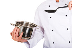 Chef's hand holding stainless steel pot and spoon Stock Photos