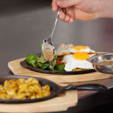 Chef's Hand Pouring Sauce On Egg Dish In Kitchen Stock Photography
