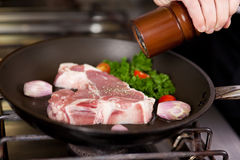 Chef's Hand Seasoning Meat In Pan Stock Photo