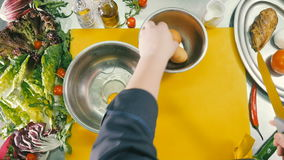 The chef`s hands break three chicken eggs into an iron bowl. The camera takes pictures from above. Two bowls and a knife lie on the kitchen stand. Salad leaves stock video