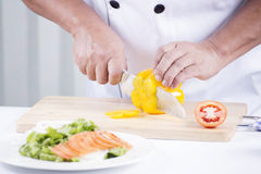 Chef's hands cutting yellow bell pepper Stock Image