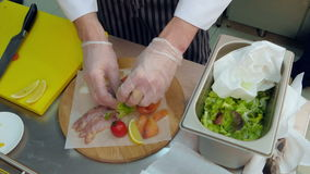 Chef`s hands in gloves putting salad on a wooden platter with different meat stock video