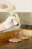 Chef's hands grinding salt to season frying hamburger patties Stock Image