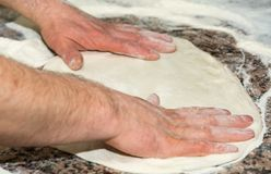 The chef`s hands knead the dough to make pizza in the kitchen. Food, italian cuisine and cooking concept.Food, italian cuisine an. D cooking concept. Preparation Royalty Free Stock Photography