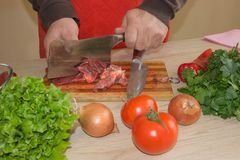 Chef`s hands with a knife cuts the meat on the wooden board in the kitchen. Cooking at home. Healthy eating and lifestyle Stock Image