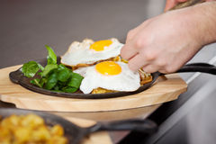 Chef's Hands Placing Fried Egg On Dish At Kitchen Counter Royalty Free Stock Photo