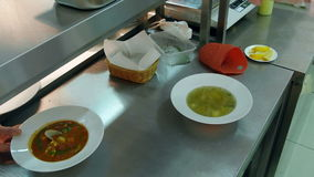Chef`s hands pouring soup into a plate and adding herbs stock footage