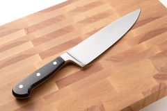 Chef's knife on wood cutting board. Background Royalty Free Stock Photos
