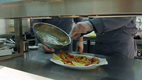 Chef`s male hands dressing cooked shrimps and veggies on a plate with sauce stock video footage