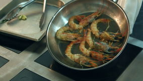 Chef`s male hands putting prawns on a frying pan stock video footage