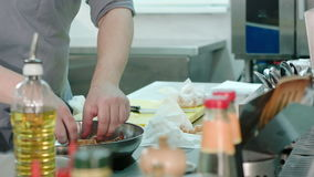 Chef`s male hands putting royal shrimps on a frying pan stock footage