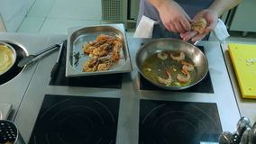 Chef`s male hands putting shrimps on a frying pan with garlic stock video