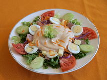Chef salad. Plate of appetizing fresh chef salad on orange tablecloth royalty free stock images