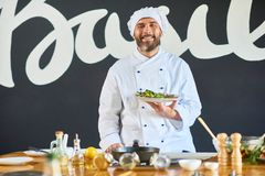 Chef with salad. Portrait of smiling chef standing with salad in the kitchen royalty free stock photography