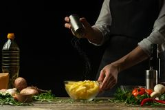 Chef salting french fries on a background with vegetables. Cooking tasty but harmful food stock photo
