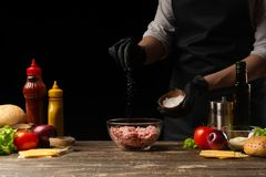 Chef salting mincemeat to create patties for a burger. Against the background with ingredients for a burger. The concept of facet. Food, tasty and fatty food royalty free stock image