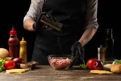 Chef salting mincemeat to create patties for a burger. Against the background with ingredients for a burger. The concept of facet. Food, tasty and fatty food royalty free stock images