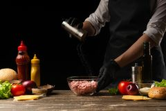 Chef salting mincemeat to create patties for a burger. Against the background with ingredients for a burger. The concept of facet. Food, tasty and fatty food stock images