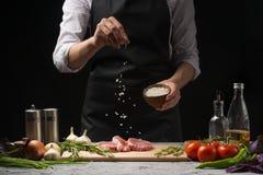 Chef salts steak grill pan. Preparing fresh beef or pork. Horizontal photo with a dark black background. stock photography