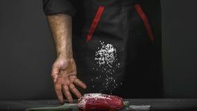 Chef salzt Fleischsteak Kochen der Fleischleiste auf Holztisch durch Kochhände, schwarzer Hintergrund des Kopientextes lizenzfreie stockfotografie