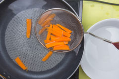 Chef scald carrot with hot water Royalty Free Stock Photography