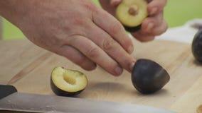 Chef schneidet reife Pflaumen mit Messer auf hölzernem Schneidebrett stock footage