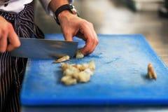 Chef schneidet rohe Garnele mit großem speziellem Messer Stockbilder