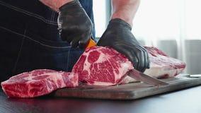 Chef schneidet rohes Fleisch auf dem hölzernen Brett mit dem Messer, Nahaufnahme stock footage
