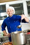Chef with scoop. Professional chef cooking in commercial kitchen with scoop and pot Royalty Free Stock Images