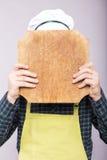 Chef se cachant derrière un hachoir en bois sur le gris Image stock
