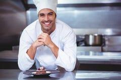 Chef se penchant sur le compteur avec un dessert photo stock