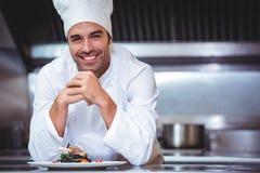 Chef se penchant sur le compteur avec un plat photos stock