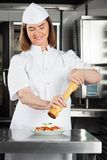 Chef Seasoning Dish With Peppermill. Female chef seasoning dish with peppermill at restaurant kitchen counter Stock Photo