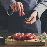 Chef seasoning filet mignon on wooden board at restaurant kitche Stock Image