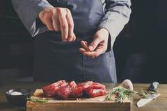 Chef seasoning filet mignon on wooden board at restaurant kitche. Man sprinkles filet mignon steaks with pepper salt. Chef working at open restaurant kitchen stock photo