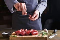 Chef seasoning filet mignon on wooden board at restaurant kitchen. Man sprinkles filet mignon steaks with pepper salt. Chef working at open restaurant kitchen stock photo