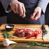 Chef seasoning rib eye steak on wooden board at restaurant kitchen Royalty Free Stock Images