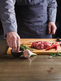 Chef seasoning rib eye steak on wooden board at restaurant kitchen Royalty Free Stock Photos