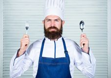 Chef serious face hold spoon and fork. Man handsome with beard holds kitchenware on white background. Cooking process stock image