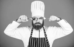 Chef serious strict face hold spoon and fork. Cooking process concept. Lets try dish. Hungry chef ready to try food. Time to try taste. Man handsome with beard royalty free stock image