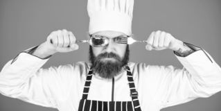 Chef serious strict face hold spoon and fork. Man handsome with beard holds kitchenware on blue background. Cooking royalty free stock images