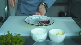 The chef serves a plate of sauce. Chef puts vegetables on a plate stock video footage