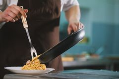 Chef serves spaghetti carbonara on the plate in restaurante Royalty Free Stock Image