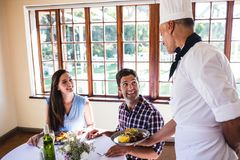 Chef serving food to young couple sitting in a restaurant. Male chef serving food to young couple sitting in a restaurant stock photo