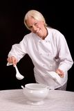 Chef serving with a ladle. Assertive posed uniformed Chef serving with ladle from tureen Stock Photo