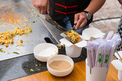 Chef Serving Stir Fried Noodles in Take Out Box. Close Up of Chef Serving Single Portion of Stir Fried Noodles in Chinese Take Out Box Stock Photography