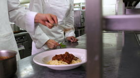 Chef serving up spaghetti and another garnishing with basil leaf stock video