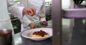 Chef serving up spaghetti and another garnishing with basil leaf stock footage